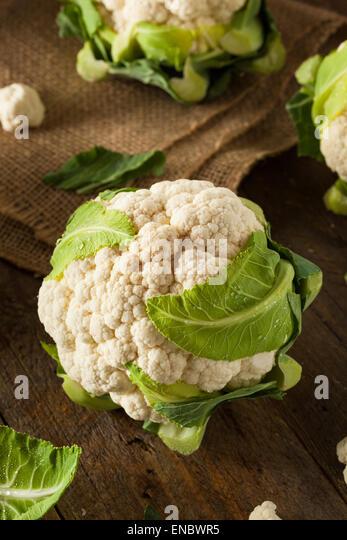 Raw Organic Cauliflower Heads with Fresh Green Leaves - Stock Image