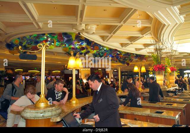 Nevada Las Vegas The Strip South Las Vegas Boulevard Bellagio hotel casino lobby ceiling glass Chihuly guests front - Stock Image