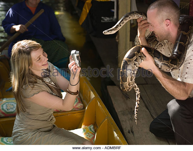 Woman taking picture of man holding snake - Stock Image