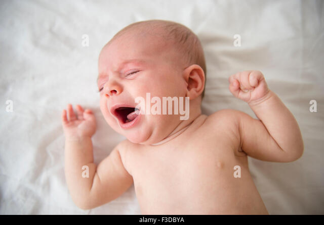 Baby girl (2-5 months) crying in crib - Stock Image