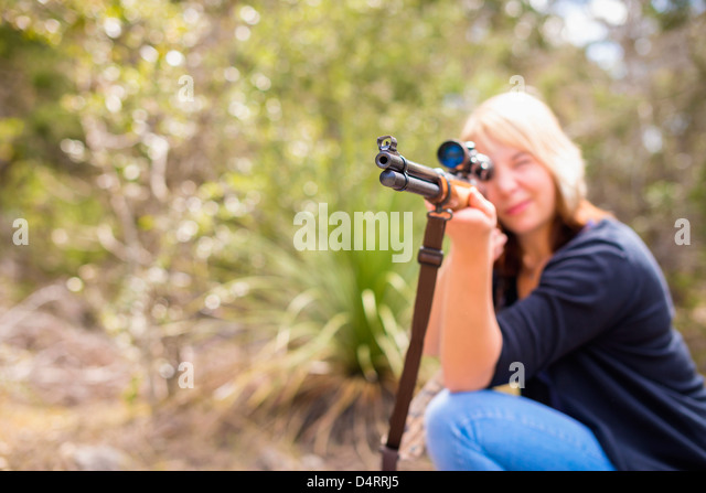 Young woman shooting a hunting rifle firearm, Female 19 Caucasian, Texas, USA - Stock Image