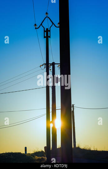 Sunrise thgrough silhouetted power poles - France. - Stock Image