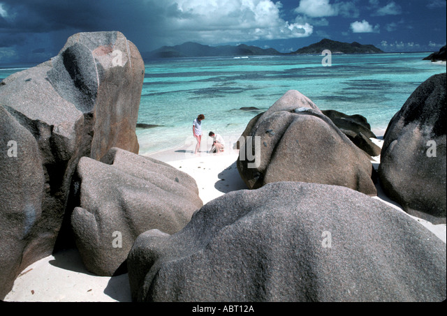 Seychelles Island of La Digue Couple on the beach surrounded by boulders - Stock Image