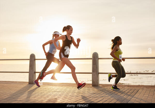 Three young women running on a road by the sea. Group of divers runners training on seaside promenade during sunset. - Stock Image