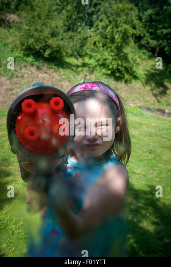 Young girl shooting a water gun in her garden. - Stock Image