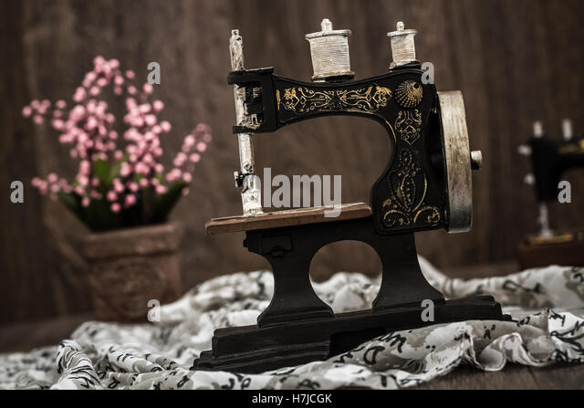 Small nostalgic decorative sewing machine on brown wooden background - Stock Image