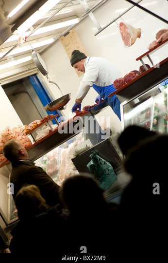 A stallholder selling cheap cuts of meat at Aberystwyth November fair market, Wales UK - Stock Image