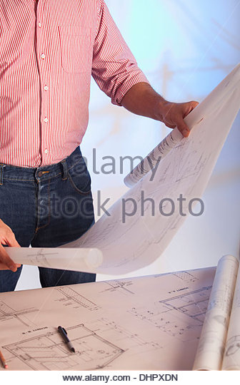 Architect holding blueprint architectural drawings - Stock-Bilder