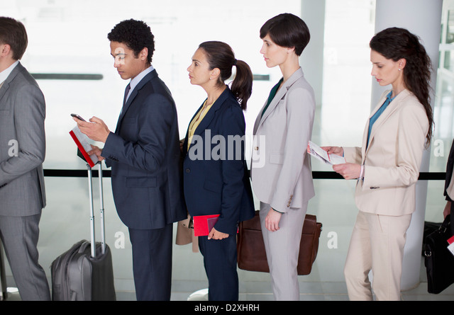 Business people standing in queue at airport - Stock Image