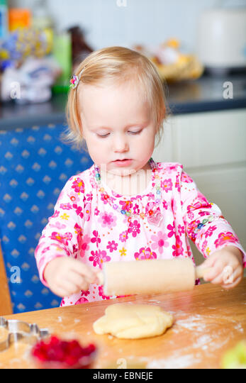 little girl rolling out dough with a rolling pin - Stock Image