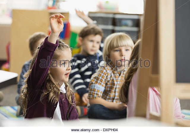 Girl sitting in elementary class with hand raised - Stock Image