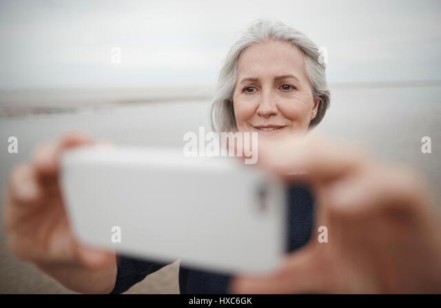 Senior woman taking selfie with camera phone on winter beach - Stock Image