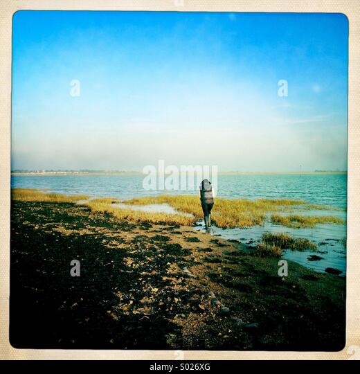 Woman walking on foreshore, Chichester Harbour, UK - Stock Image