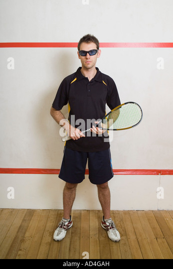 A man standing on a squash court - Stock Image