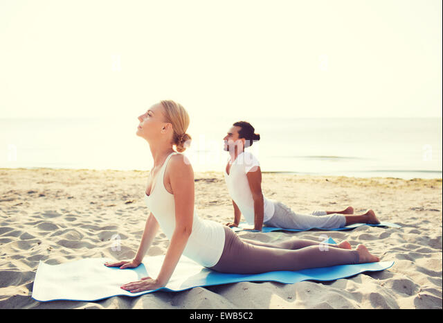 couple making yoga exercises outdoors - Stock Image