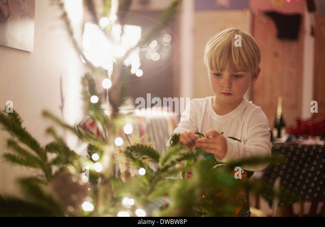 Young boy decorating christmas tree - Stock Image