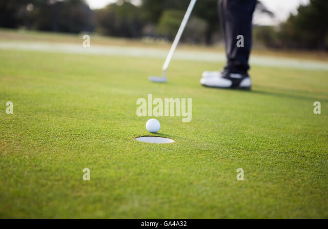 Close up of golf ball and a hole - Stock Image