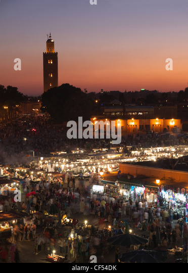 Morocco, Marrakesh, People at Djemaa el Fna square with Koutoubia Mosque at night - Stock Image