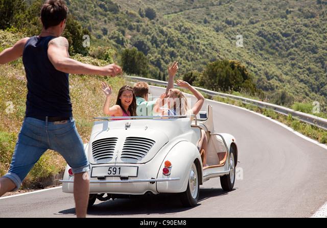 Convertible car driving past hitchhiker - Stock-Bilder