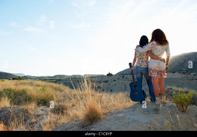 Women watching the sun set - Stock-Bilder