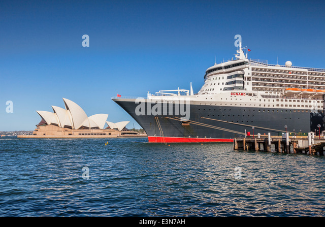 Cunard liner Queen Mary 2 berthed at Circular Quay, Sydney, with Sydney Opera House in the background. - Stock Image