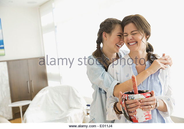 Affectionate mother and daughter preparing to paint - Stock Image