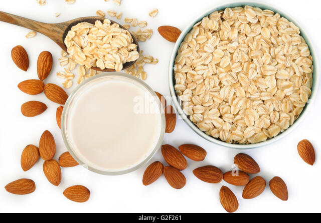 almond milk in glass with oats - Stock Image