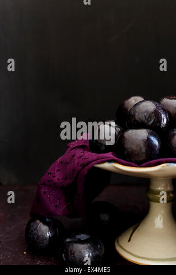 Whole Plums on a Cake Stand - Stock Image