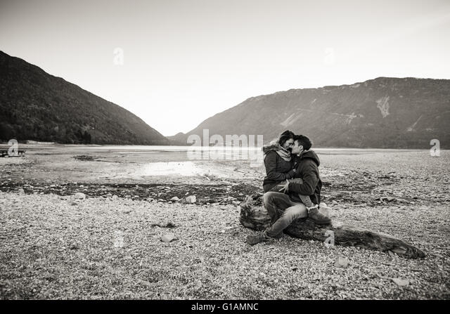 Young couple having a romantic date at the lake, they are hugging and sitting on a trunk on the beach, love and - Stock Image