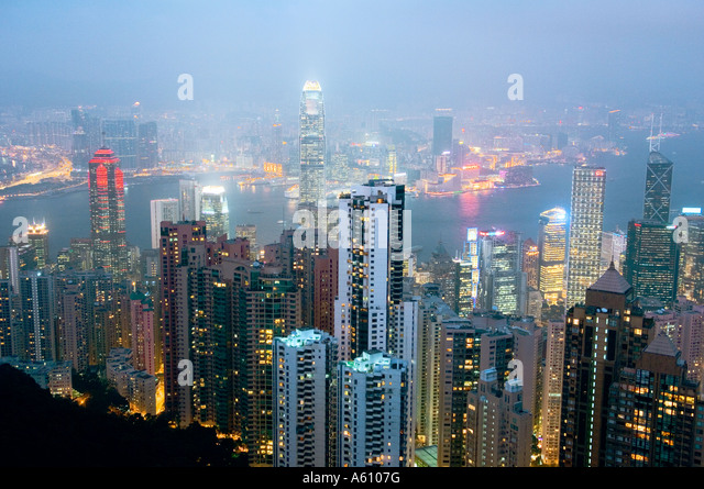Hong Kong Island. Dusk view from Victoria Peak over city centre skyscrapers and Hong Kong Harbour to Kowloon shore - Stock Image
