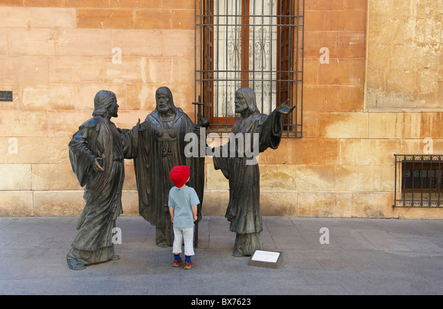 Young boy looking at religious statues in historic square - Stock Image