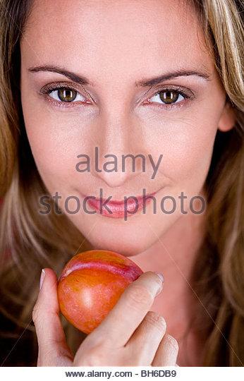 A mid adult woman holding a plum, close-up - Stock-Bilder