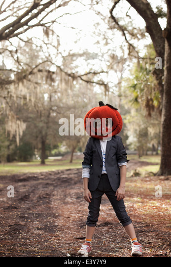 Portrait of boy in forest wearing pumpkin head - Stock Image