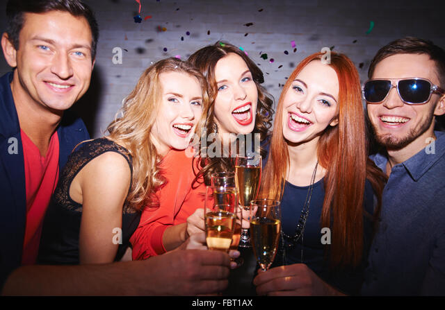 Group of joyful friends toasting with champagne - Stock Image