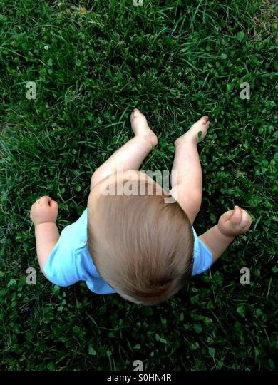 Baby boy sitting on the grass  outside - Stock Image