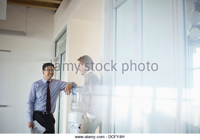 Co-workers talking around water cooler - Stock Image