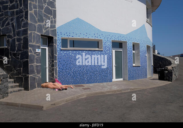 Females sunbathing in the doorway of the fish market at Los Abrigos, Tenerife, Canary Islands, Spain. - Stock Image