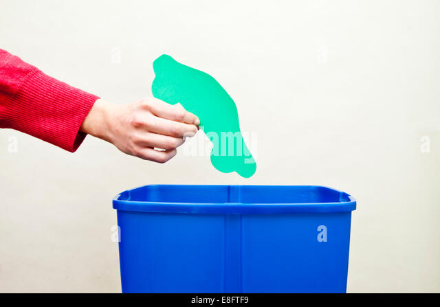Woman's hand dropping car shape paper cut out into recycling bin - Stock Image