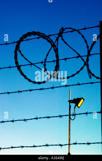 Barbed Wire Fencing &  A Security Light Set Against A Clear Blue Sky. - Stock Image