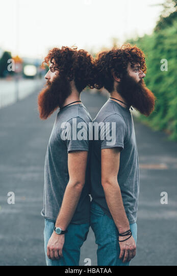Portrait of identical adult male twins with red hair and beards back to back on sidewalk - Stock Image