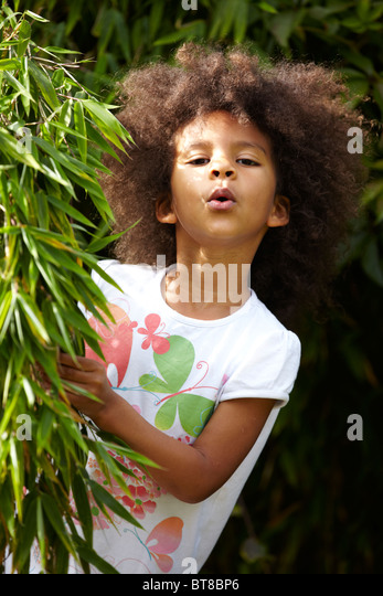 young girl, child, mixed race peeping out behind bamboo plant outside - Stock Image
