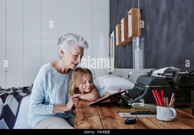 Grandmother and granddaughter looking at tablet at home - Stock Image