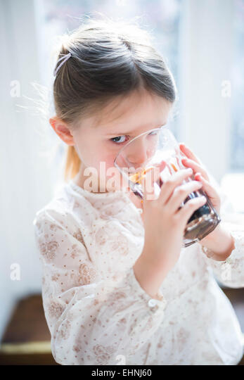 5 year-old girl drinking soft drink. - Stock Image