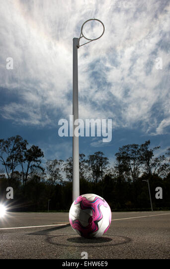 Netball resting on the ground, positioned in the shadow of the goal post. - Stock Image