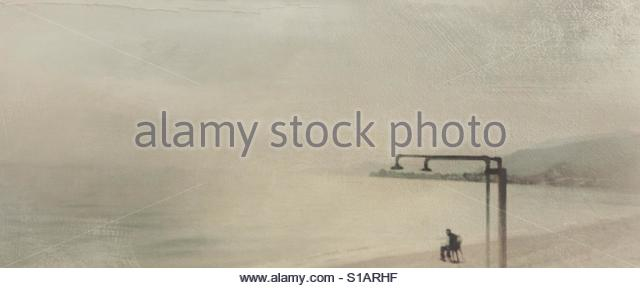 A man fishing at a beach in Greece' - Stock Image