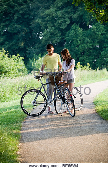 A young couple standing with bicycles holding a map - Stock Image