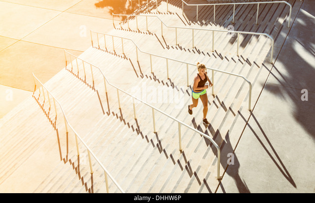Woman running up stairs - Stock Image
