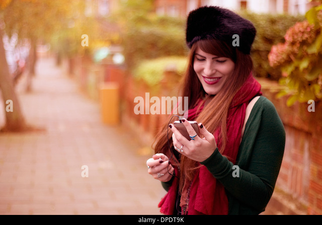 Young woman wearing winter clothing, holding smartphone - Stock Image
