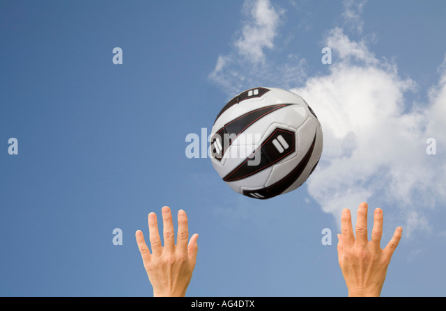 STUDIO Two hands reaching up to a netball in a blue sky - Stock Image