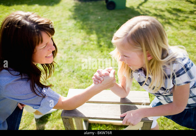 Mother and daughter arm wrestling - Stock Image